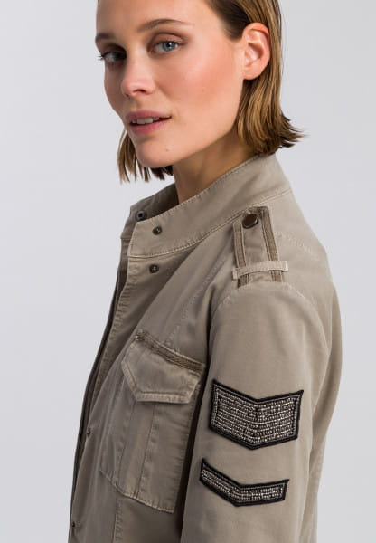 Jacket with embroidered bead-badges